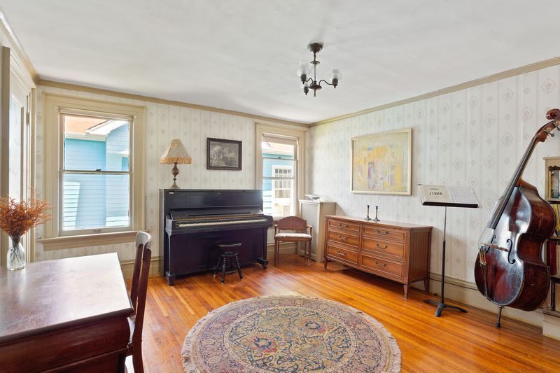 A bedroom with hardwood floors, a small chandelier, a cello, a sheet music stand, a piano, and two windows.