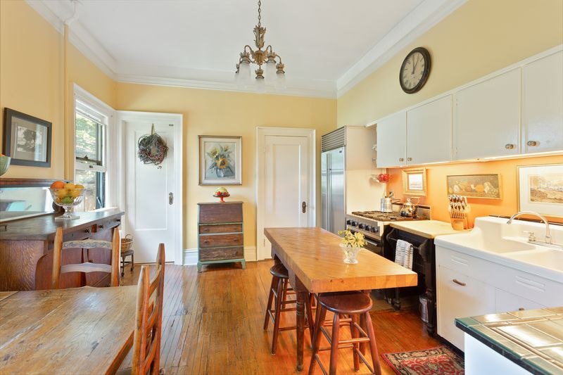 An eat-in kitchen with hardwood floors, white cabinetry, light yellow walls, and two wooden tables with chairs.