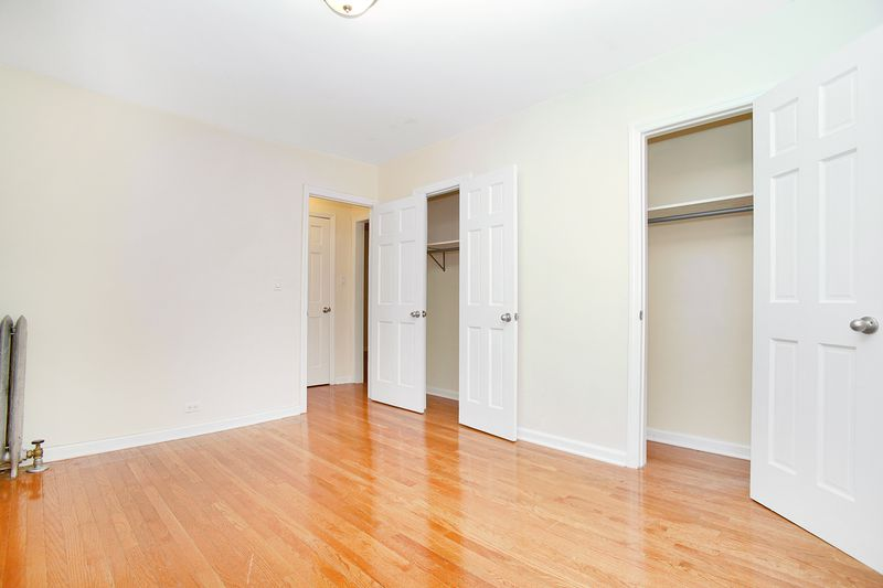 A bedroom with two large closets, hardwood floors, and base moldings.