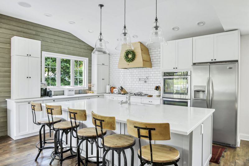 An open kitchen with a large island, three hanging lamps, and white cabinetry.