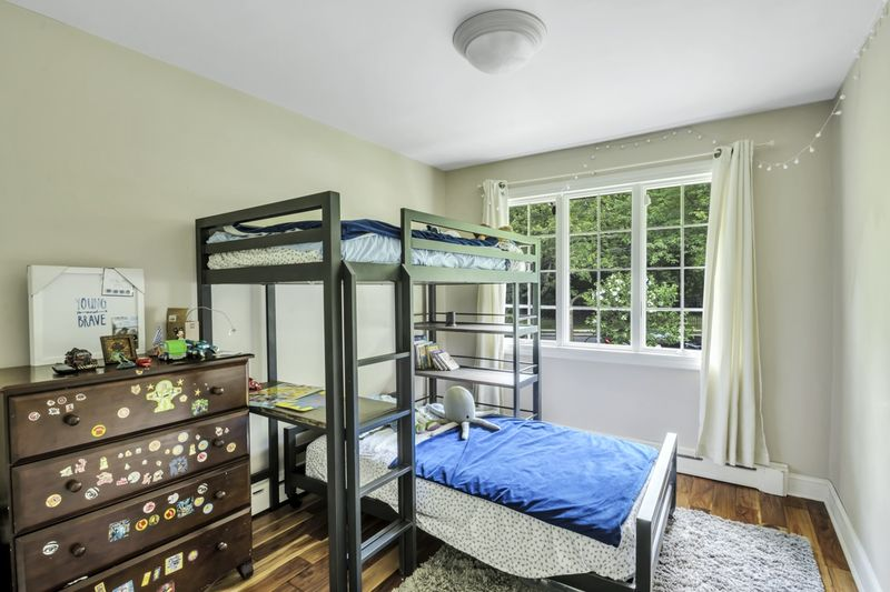 A bedroom with a large window, base moldings, and a bunk bed.