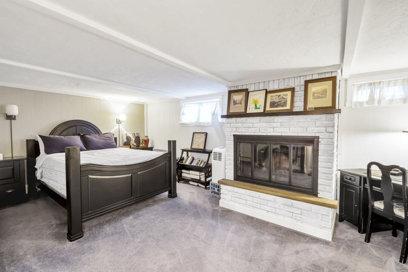 A basement bedroom with a fireplace, a large bed, and a wooden desk.