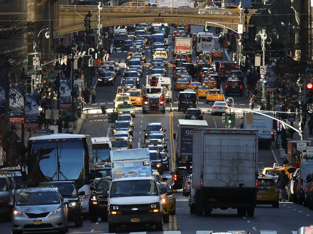 A congested road in Manhattan packed with cars, trucks, and buses bumper-to-bumper.