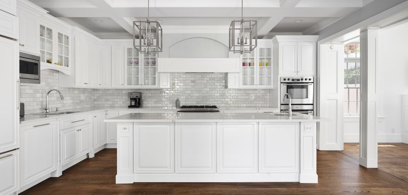 A kitchen with a large island with quartz countertops, hardwood floors, and white cabinetry.