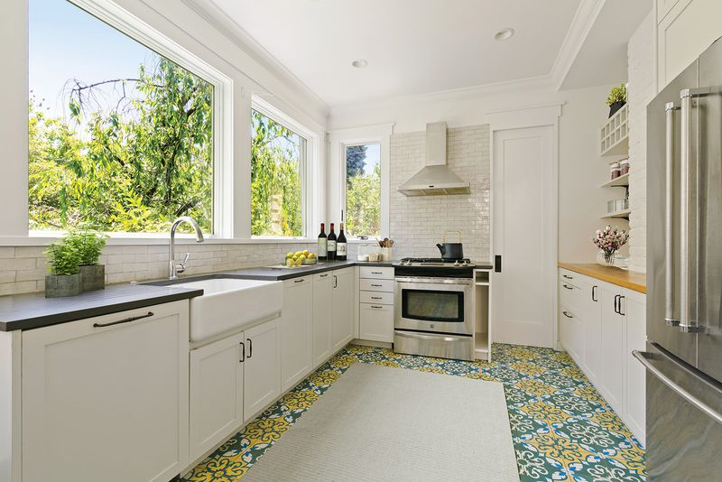 A kitchen with colorful mosaic tiles and large windows.
