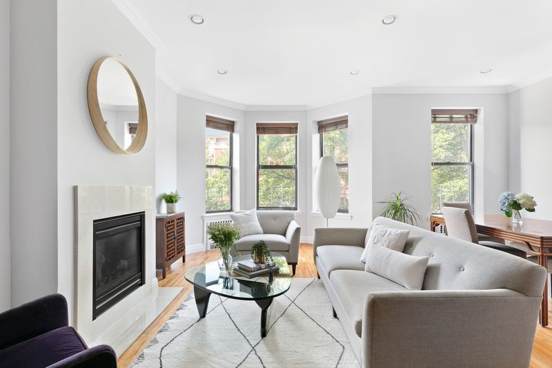 Living room with gray sofa, cream rug, and ivory gas fireplace.