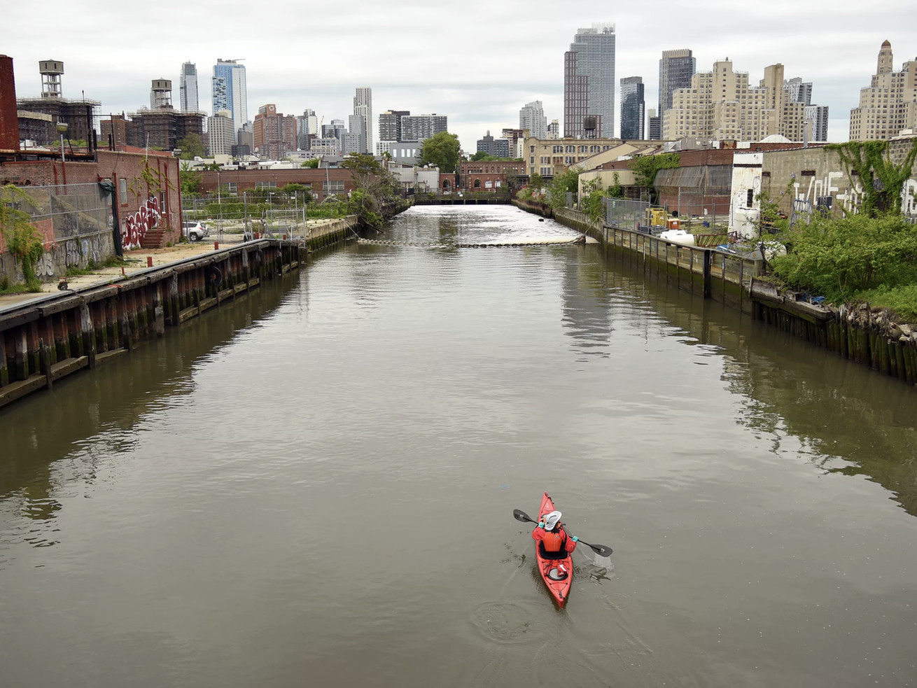 A kayaker paddles in the Gowanus canal, the banks of which are a major neighborhood rezoning has been proposed by the city.