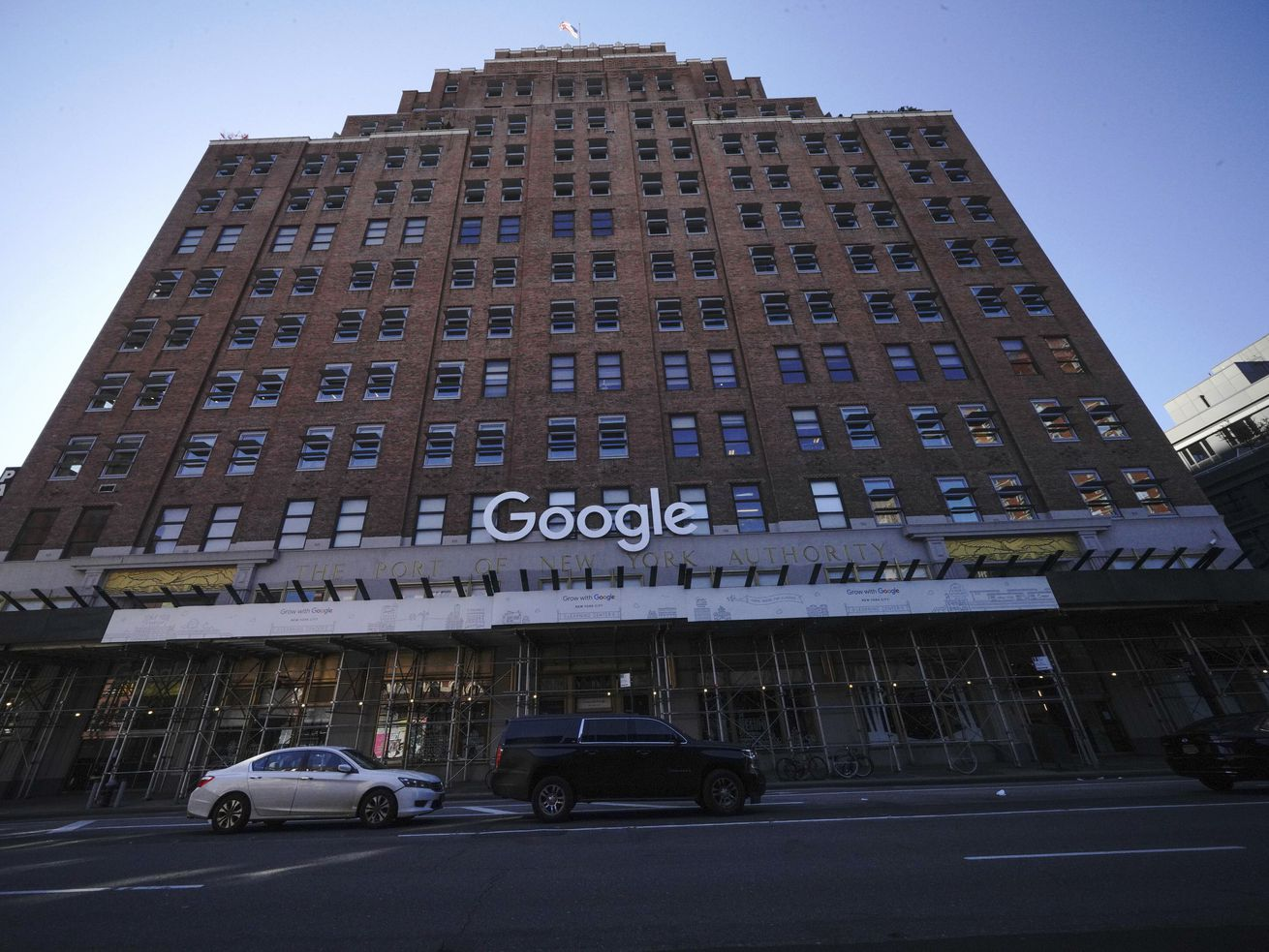 """A high-rise brick building with a bright white """"Google"""" sign on the facade."""