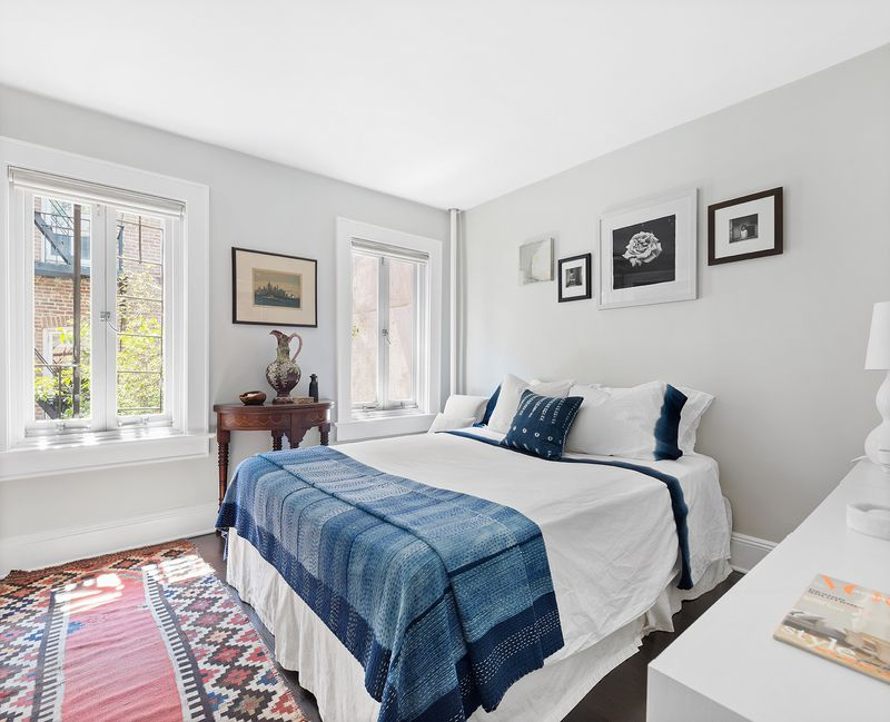A bedroom with a large bed, two framed windows, a colorful rug, grey walls, and base moldings.