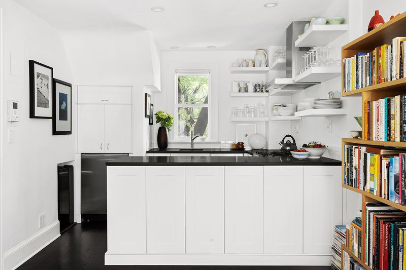 An open kitchen with a window, an island, and white cabinetry.