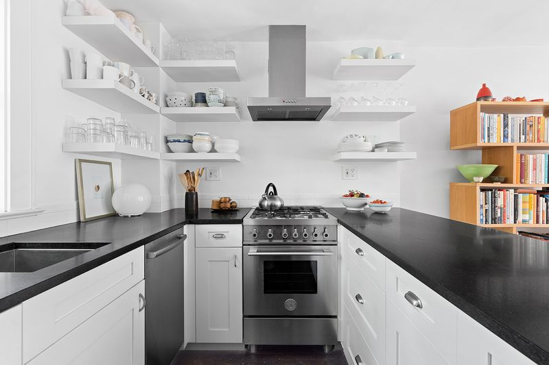 A kitchen with white cabinetry, an island, and stainless steel appliances.