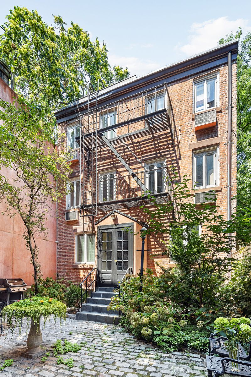 The back of a four-story carriage house with brick tiles, a planter fountain, a barbecue grill, and several plants.