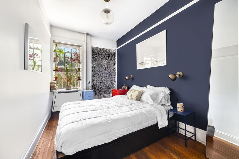 A bedroom with a dark blue wall, a bed, a small window with planters, and hardwood floors.