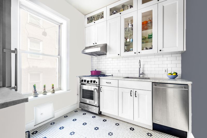 A kitchen with hexagon pattern floor tiles, a dishwasher, white cabinetry, and a large window.