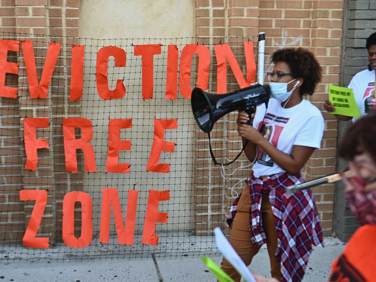 """Demonstrators hold up a neon orange banner that states, """"Eviction Free Zone."""""""