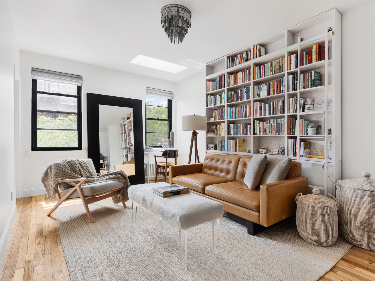 Living room with a brown sofa, wall of bookshelves, two windows, and a skylight.