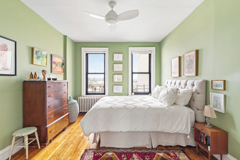 A bedroom with green walls, two windows, a ceiling fan, hardwood floors, and a bed.