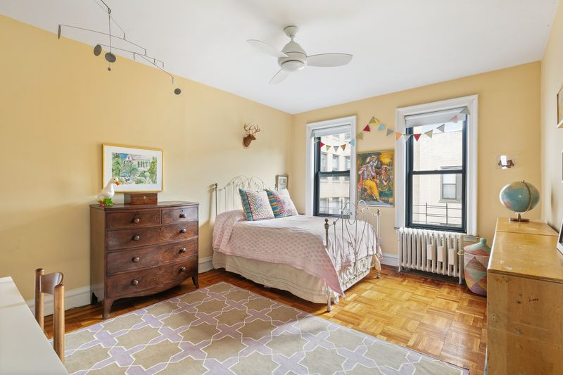 A bedroom with yellow walls, a ceiling fan, a small bed, and two windows.