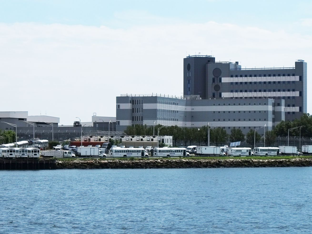 A high-rise jail on Rikers Island with white Department of Correction buses lined in front of it.