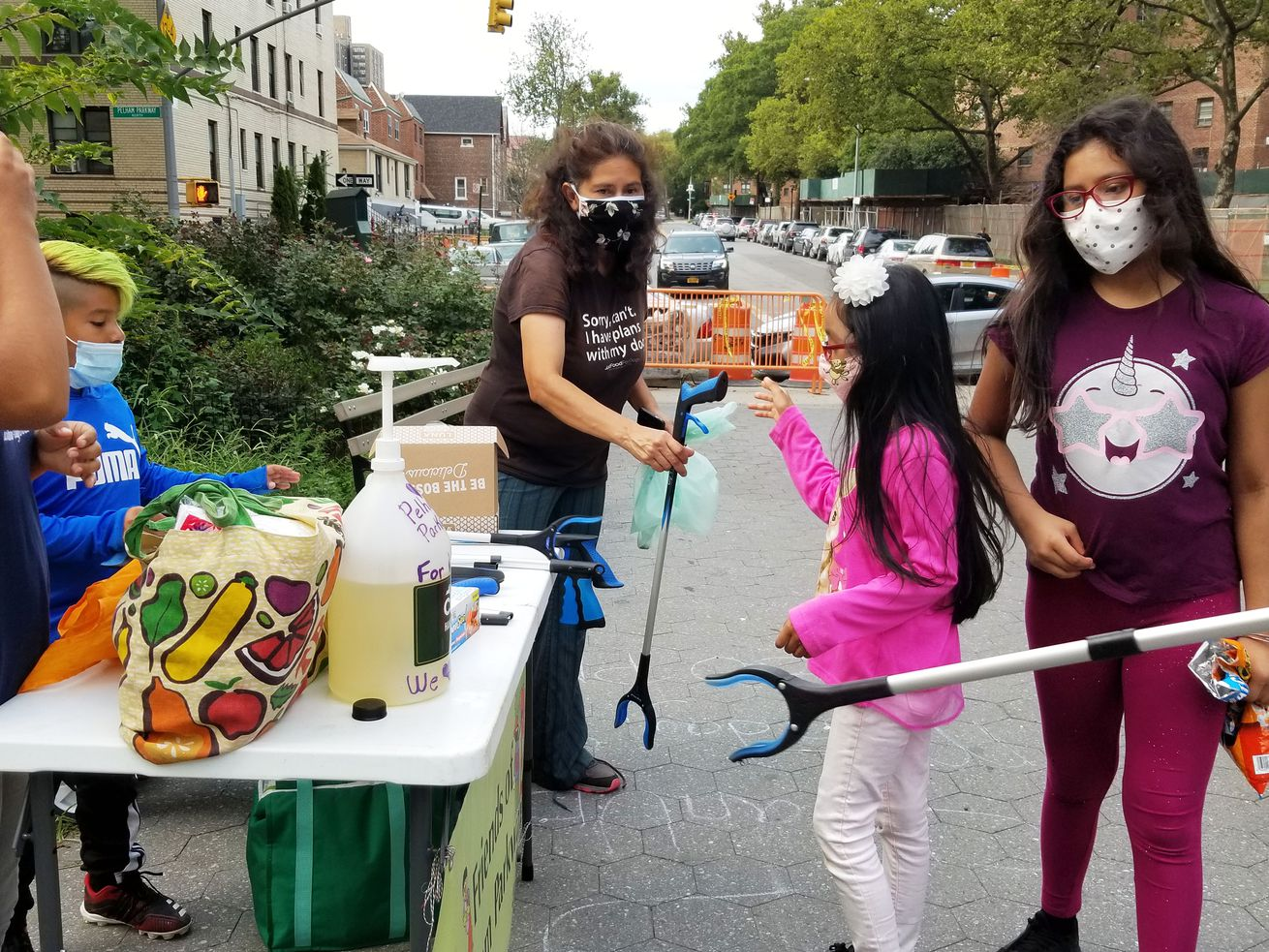 A woman hands a young girl a claw-life trash grabber to clean Pelham Parkway in the Bronx.