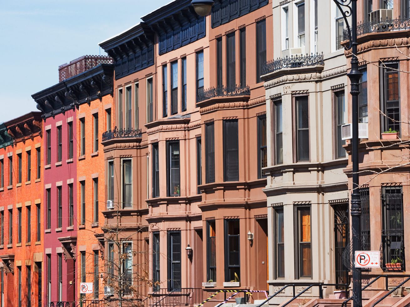 A row of brownstones and bright brick apartment buildings on a block in Brooklyn.