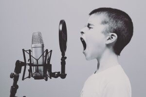 Black and white picture of a boy screaming in a microphone