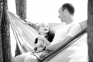 Black and white picture of a man holding a baby in a white hammock